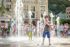 KYIV, UKRAINA SIERPIEŃ 13, 2017: Szczęśliwi dzieciaki zabawę bawić się w wody miejskiej fontannie na gorącym letnim dniu Obraz Royalty Free