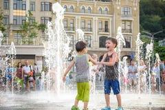 KYIV, UKRAINA SIERPIEŃ 13, 2017: Szczęśliwi dzieciaki zabawę bawić się w wody miejskiej fontannie na gorącym letnim dniu Fotografia Royalty Free