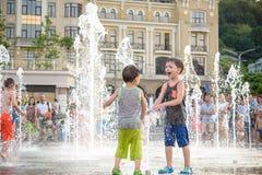 KYIV, UKRAINA SIERPIEŃ 13, 2017: Szczęśliwi dzieciaki zabawę bawić się w wody miejskiej fontannie na gorącym letnim dniu Obrazy Royalty Free