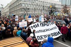KYIV UKRAINA: Tusentals aktivt folk med anti--regering bunners som rusar till det största mötet under protesten Arkivfoton