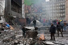 KYIV, UKRAINE: Active people burn fire past barricades after night fights on the destroyed winter street during the riot Stock Image