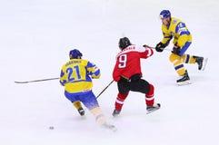 Ice Hockey 2017 World Championship Div 1 in Kyiv, Ukraine. KYIV, UKRAINE - APRIL 25, 2017: Alex RAUCHENWALD of Austria C fights for a puck with Denys ISAYENKO L Royalty Free Stock Photo