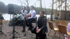 KYIV, UKRAINE - APRIL 21, 2019: The band plays the guitar, percussion instrument and sings a song at the wedding stock video footage