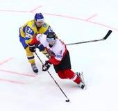 Ice Hockey 2017 World Championship Div 1 in Kyiv, Ukraine. KYIV, UKRAINE - APRIL 25, 2017: Denys ISAYENKO of Ukraine Yellow fights for a puck with Alexander Royalty Free Stock Photos