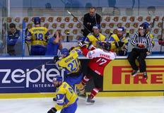 Ice Hockey 2017 World Championship Div 1 in Kyiv, Ukraine. KYIV, UKRAINE - APRIL 25, 2017: Sergiy KUZMIK of Ukraine #27 fights for a puck with Manuel GANAHL of Stock Image