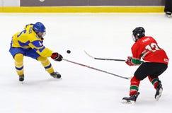 2018 Ice Hockey U18 World Championship Div 1, Kyiv, Ukraine. KYIV, UKRAINE - APRIL 17, 2018: Serhi LOHACH of Ukraine L fights for a puck with Kristof PAPP of Royalty Free Stock Photo
