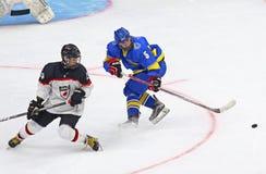 2018 Ice Hockey U18 World Championship Div 1, Kyiv, Ukraine. KYIV, UKRAINE - APRIL 14, 2018: Shota KANEKO of Japan L fights for a puck with Serhi LOHACH of Royalty Free Stock Images
