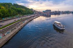 Tourist boat on Dnipro river. The River Port and Poshtova Square on Podil in the historical district of Kyiv, Ukraine. Kyiv, Ukraine - April 28, 2019: Tourist stock image