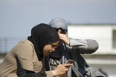 Kyiv Ukraine - April 21, 2018: two young Muslim women in sun glasses looking in smartphone stock photos