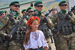 Kyiv, Ukraine - August 24, 2014: The young girl in national dress posing surrounded by soldiers in the Independence Day of Ukraine Royalty Free Stock Photography