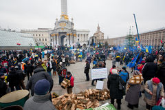 KYIV, UKRAINE: Crowd of demonstrators harvest wood. Crowd of demonstrators harvest wood for fires, occupying main Maidan square and require to sign the documents Royalty Free Stock Photos