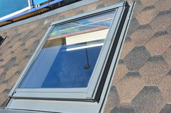 Close up on attic skylight window repair with waterproofing membrane on asphalt shingles roof. Roofing Construction. KYIV, UKRAINE - may, 27, 2019: Close up on stock photo