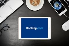 Apple iPad Gold with with Booking.com app on the screen. Kyiv, Ukraine - Fabruary 6, 2018: Apple iPad Gold with Booking.com  app on the screen on black desk with Stock Photos