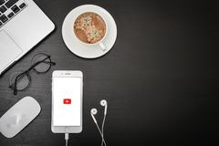 Apple iPhone 8 plus with YouTube app. Kyiv, Ukraine - Fabruary 6, 2018: Apple iPhone 8 plus with YouTube app on the screen lying on black desk with headphones Royalty Free Stock Photos