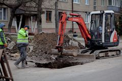 Kyiv, Ukraine - February 22, 2019: A group of road workers from public utilities in reflective special vests are discussing an