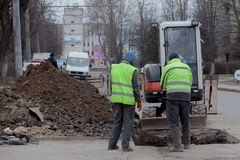 Kyiv, Ukraine - February 22, 2019: A group of road workers from public utilities in reflective special vests are discussing an. Emergency when digging a hole to stock images