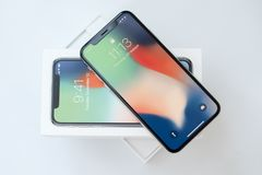 KYIV, UKRAINE - 26 JANUARY, 2018: New Iphone X smartphone model close up. Newest Apple Iphone 10 mobile phone device on. White branded Apple box on white table Royalty Free Stock Photography