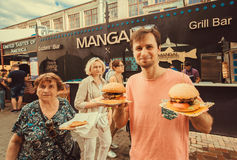 Man bought a burger and bearing to share with the family on food-court of outdoor Street Food Festival. KYIV, UKRAINE - JUL 23: Man bought a burger and bearing royalty free stock photos