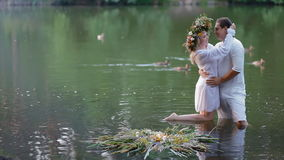 KYIV, UKRAINE - 3 July 2015: Young couple in national clothes in the river. Woman wears a big wreath on her hair. Ducks are swimming in the water. Ivana Kupala stock video
