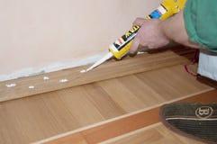 Repairman installing skirting board oak wooden floor with caulking gun silicone from cartridge. Flooring with wooden batten repair. KYIV, UKRAINE - June, 13 royalty free stock image