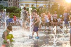 KYIV, UKRAINE LE 13 AOÛT 2017 : Les enfants heureux ont l'amusement jouant dans la fontaine d'eau de ville le jour chaud d'été Photo libre de droits