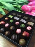 Kyiv, Ukraine le 7 mars 2018, bonbons fabriqués à la main au CHARME CHOCHOLATE dans une boîte foncée, décorée des tulipes Celebra Images stock