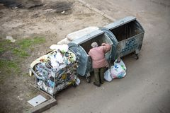 KYIV, UKRAINE MARCH 31, 2019: A homeless man looking for food in a garbage dumpster. Urban Poverty. A homeless man looking for food in a garbage dumpster. Urban stock photo
