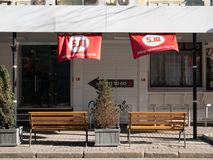 Two empty wooden benches at street cafe terrace with red flag of ukrainian liberal political party 5.10. KYIV, UKRAINE - MARCH 13, 2019: Two empty wooden benches royalty free stock images