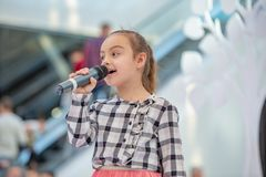 Kyiv, Ukraine March 03.2019. UKFW. Ukrainian Kids Fashion Day. Girl holds microphone in her hand while performing song at the stock image