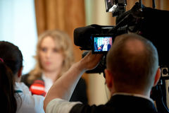 TV camera shoots an interview. Reporter viewed from back. stock photos