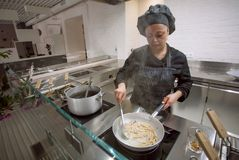 Cooking chef making italian food pasta or spaghetti at open kitchen inside modern restaurant. KYIV, UKRAINE - MAY 26: Cooking chef making italian food pasta or Royalty Free Stock Photo