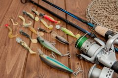 Kyiv, Ukraine- May 15, 2019 Fishing tackle - fishing spinning, hooks and lures on wooden background with copy space.  royalty free stock images