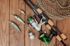 Kyiv, Ukraine- May 15, 2019 Fishing tackle - fishing spinning, hooks and lures on wooden background with copy space.  stock photo