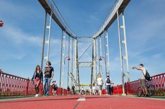 Kyiv, Ukraine - May 18, 2019. Park bridge over the Dnipro river. People walking along the pedestrian bridge on weekend royalty free stock images