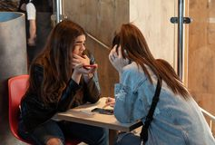 Young people eating in a Mcdonald`s. KYIV, UKRAINE - May 05, 2017: Young people have a rest and eating in a Mcdonald`s in Kyiv, Ukraine. Mcdonald`s is a very stock photo