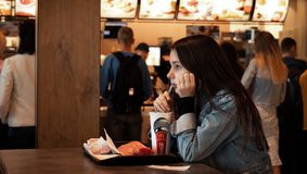 Young people eating in a Mcdonald`s. KYIV, UKRAINE - May 05, 2017: Young people have a rest and eating in a Mcdonald`s in Kyiv, Ukraine. Mcdonald`s is a very royalty free stock images
