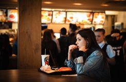Young people eating in a Mcdonald`s. KYIV, UKRAINE - May 05, 2017: Young people have a rest and eating in a Mcdonald`s in Kyiv, Ukraine. Mcdonald`s is a very stock image