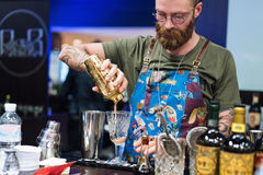 Kyiv, Ukraine - 30 october, 2016: Barman festival. Handsome bearded hipster with long beard and mustache holding shaker. Kyiv, Ukraine - 30 october, 2016: Barman royalty free stock images