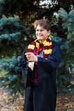 Boy in glasses stands in autumn park with gold leaves holds wand in his hands, wears in black robe stock photography
