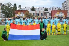 KYIV, UKRAINE - October 10, 2017: Flag of the Netherlands agains. T the background of football players of the youth team during the qualification match of the royalty free stock photo