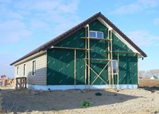 House insulation with installing siding. Plastic siding and insulation membrane on house. KYIV, UKRAINE - October 31, 2018: House insulation with installing royalty free stock images