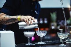 A tattooed bartender pours liquor from a shaker into a champagne glass royalty free stock image