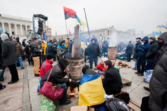 KYIV, UKRAINE: Young people with the flags sitting by the barrel with fire on the cold occupying street Stock Photography