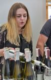 Kyiv Wine Festival by Good Wine in Ukraine. Woman sommelier pours white wine at Kyiv Wine Festival booth. 77 winemakers from around the world took part big stock photo