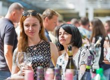 Kyiv Wine Festival by Good Wine in Ukraine. Young women taste white sparkling wine at Kyiv Wine Festival. 77 winemakers from around the world took part in the royalty free stock photo