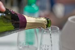 Kyiv Wine Festival by Good Wine in Ukraine. Pouring white sparkling wine closeup at Kyiv Wine Festival. 77 winemakers from around the world took part in the big royalty free stock photography