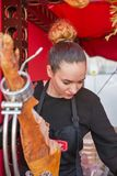 Kyiv Wine Festival by Good Wine in Ukraine. Unrecognized young woman chef carefully cuts the pork leg jamon thin slices at Kyiv Wine Festival outdoor food court Stock Photo