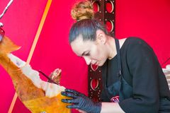 Kyiv Wine Festival by Good Wine in Ukraine. Unrecognized young woman chef carefully cuts the pork leg jamon thin slices at Kyiv Wine Festival outdoor food court Stock Photography