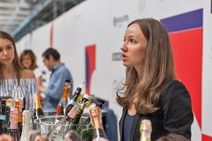 Kyiv Wine Festival by Good Wine in Ukraine. Young woman sommelier presents its sparkling wine at Kyiv Wine Festival booth. 77 winemakers from around the world stock photography