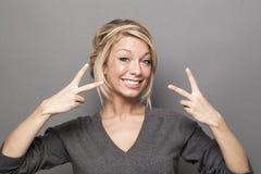 Kyla att le den unga blonda kvinnan med 2 v-tecken för fred eller seger Arkivfoto